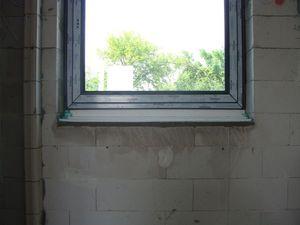 Montaż warstwowy. Środkowy i dolny fragment ościeży okiennej z zamontowanym oknem jednodzielnym systemu aluplast ideal 7000 w kolorze grafitowym.