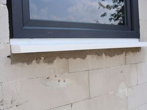 Dolny fragment ościeży okiennej z zamontowanym oknem jednodzielnym systemu aluplast ideal 7000. Konstrukcja szczelnie oparta o ciepły parapet.