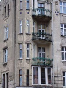 Zniszczona fasada kamiennicy. Zły dobór stolarki okiennej.