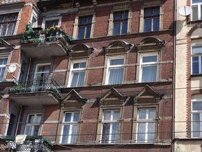 Centrum Poznania. Zniszczona fasada kamiennicy. Zły dobór stolarki okiennej.
