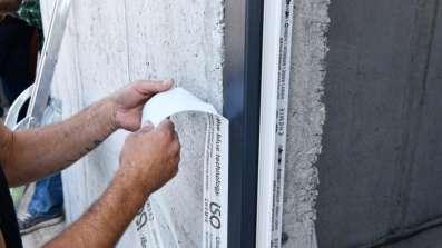Wyklejanie folii okiennej do ramy podczas ciepłego montażu okna